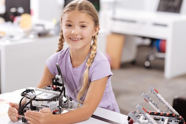 私の新しいサイバー友達。ロボット研究室に座って、喜びを表現しながらサイバーロボットを保持している幸せな喜びの女の子の笑顔