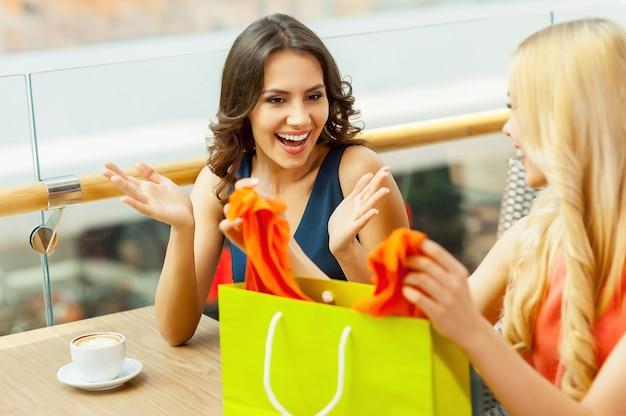 Мое новое платье. счастливые женщины вместе распаковывают сумку для покупок