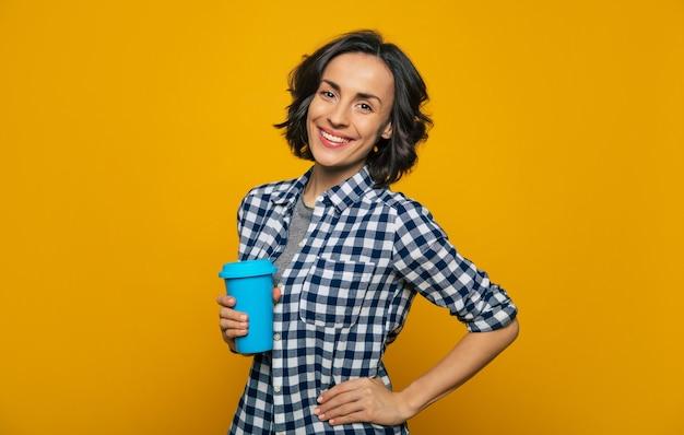 Моя новая термокружка! молодая привлекательная студентка в повседневной одежде, улыбаясь в камеру, держит в одной руке свою любимую удобную синюю термокружку, а вторую держит на бедре.