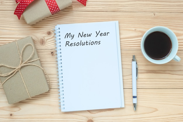 My new year resolutions word with notebook, black coffee cup and pen