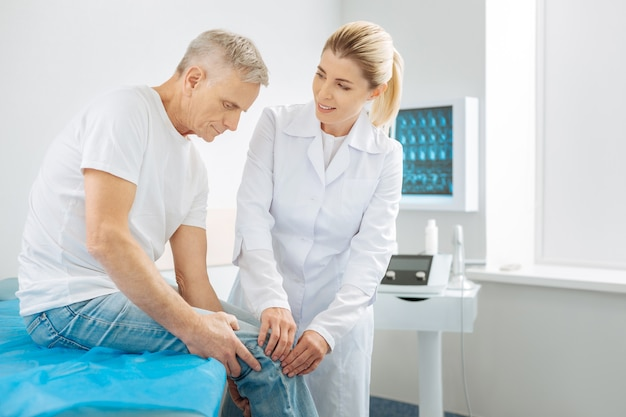 My patient. happy positive delighted woman smiling and looking at the elderly man while checking his knee