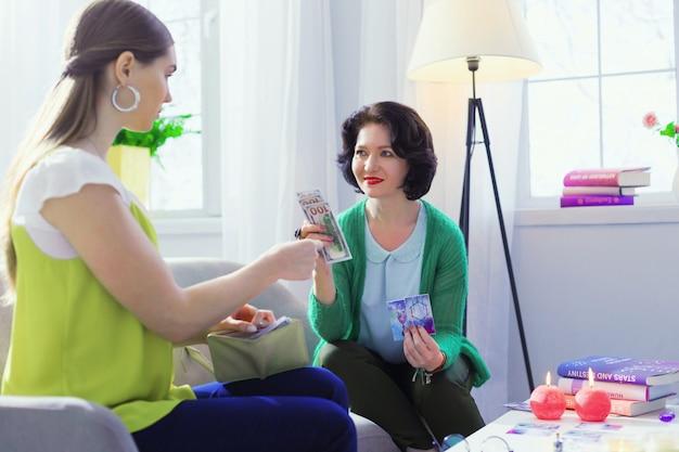 Моя оплата. позитивная брюнетка женщина улыбается, принимая деньги за свои услуги