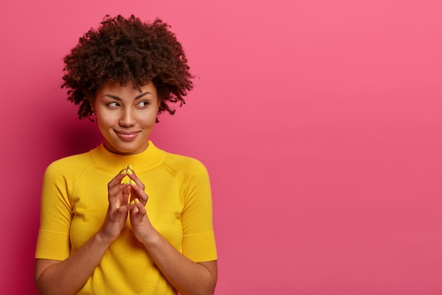 My plan is perfect. pretty african american woman schemes something, steepls fingers and looks with cunning expression aside, smiles sly, poses over pink wall, copy space aside for your promo