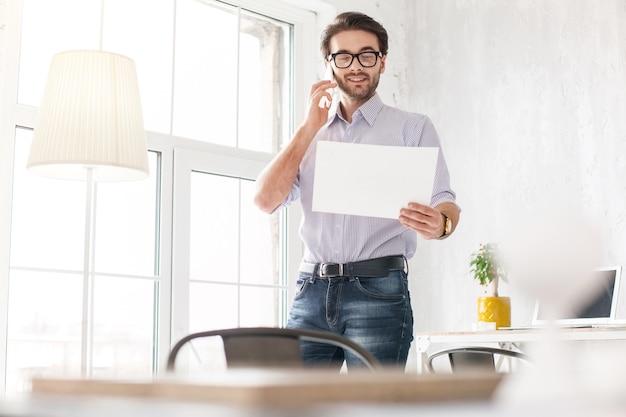 私の計画。電話で話し、紙を持っているプロの若い男