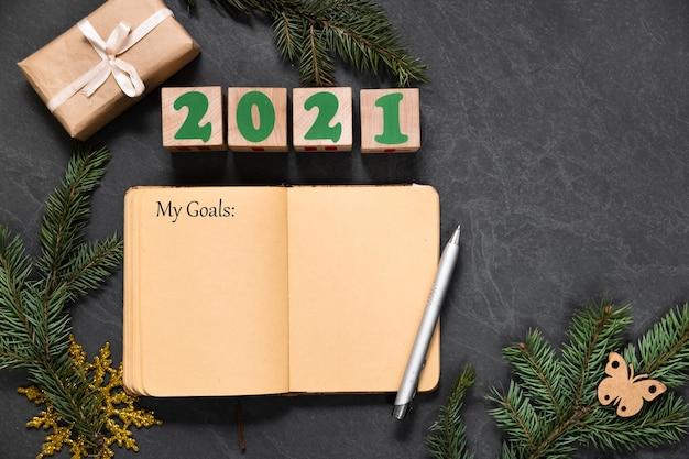 내 계획과 목표는 크리스마스 또는 새해 전에 어두운 테이블에 노트북에 적혀 있습니다. 복사 공간이있는 친구를위한 선물 목록