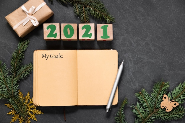 My plans and goals list in notebook on the dark table before christmas or new year. list of gifts for friends with copy space