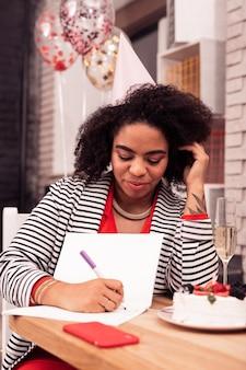 Мои планы. приятная милая женщина пишет список дел, сидя в кафетерии