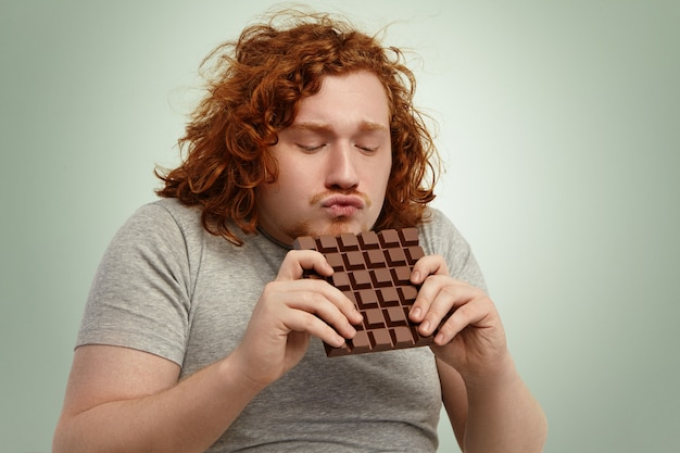 My precious! portrait of funny red-haired overweight young man addicted to sugar wearing grey t-shirt holding large bar of chocolate with both hands, pouting lips, can't wait to bite some off