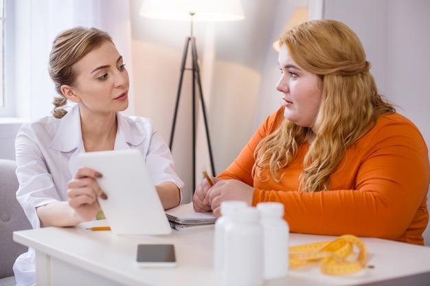 Моя профессия. решительный опытный диетолог разговаривает с толстой женщиной и держит ее таблетку