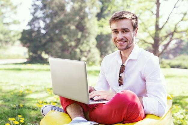 私のレクリエーション。椅子に座って彼のラップトップで作業している陽気な若い男