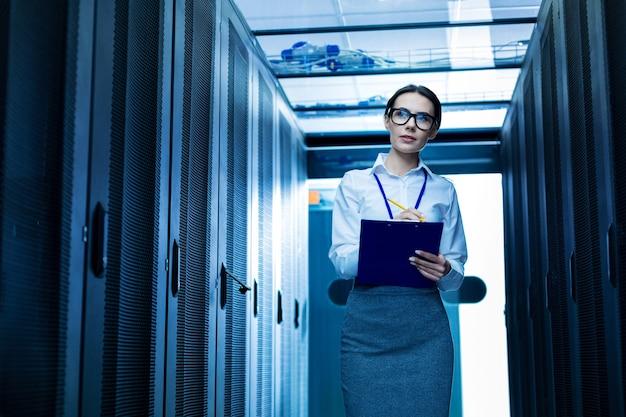 Мой отчет. вдохновленная серьезная женщина делает заметки и стоит новые серверные шкафы