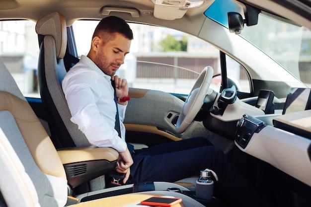 私の安全。安全を気にしながらシートベルトを締める真面目な青年