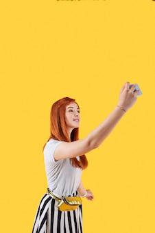 내 셀카. 셀카를 복용하는 동안 스마트 폰 카메라를 찾고 긍정적 인 빨간 머리 여자