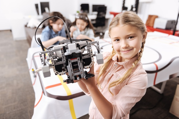 私の成功したプロジェクト。彼女の同僚がプロジェクトに取り組んでいる間、学校に立って電子ロボットを持っている勤勉な笑顔の喜んでいる女の子