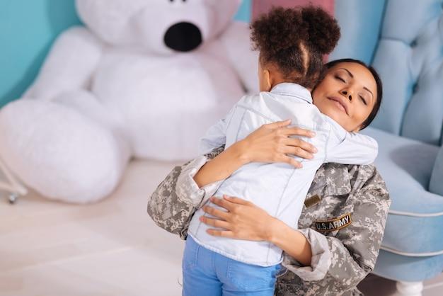 Моя милая девочка. сентиментально тронутая добрая женщина обнимает своего ребенка после того, как она преподнесла ей подарок, приветствуя ее по прибытии