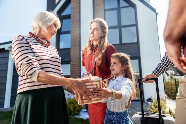 내 연인. 그녀의 예쁜 손녀를 보면서 세미 위치에 서있는 아름다운 금발의 여자