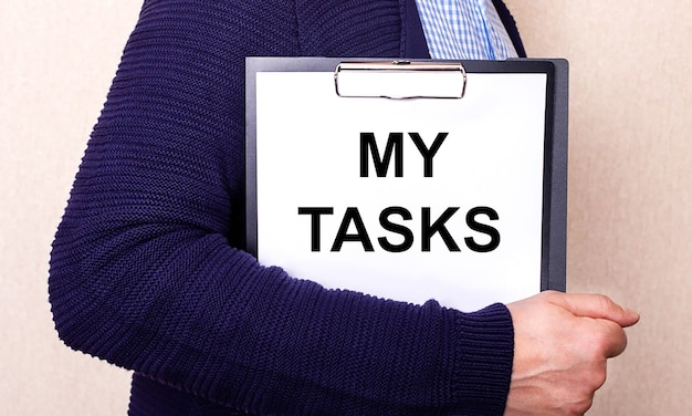 My tasks is written on a white sheet held by a man standing sideways
