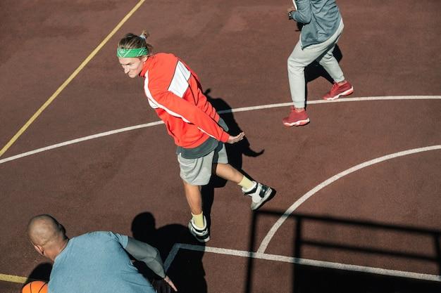 私のチーム。バスケットボールのグラウンドに立っている間彼のチームメンバーを見ている素敵な若い男