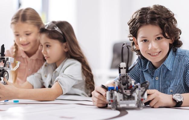 私の技術プロジェクト。学校に座って、ロボットを持ってプロジェクトをデモンストレーションしながら技術クラスを楽しんでいる陽気な明るい小さな科学者