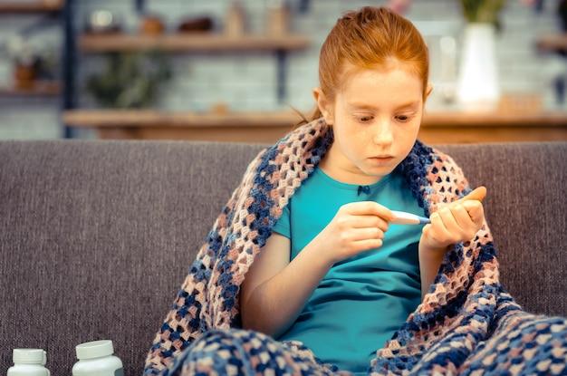 Моя температура. расстроенная эмоциональная девушка держит электронный термометр, проверяя свою температуру