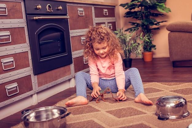 私のおもちゃ。彼女のおもちゃを見ながら頭を下げる陽気なブロンドの女の子