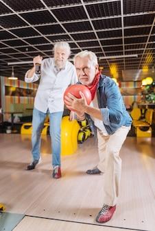 Мой ход. радостный пожилой мужчина концентрируется на игре, готовясь нанести удар