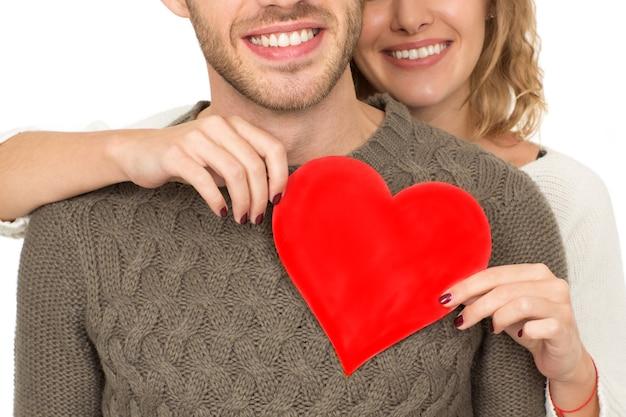 내 발렌타인. 그녀의 남자의 가슴에 붉은 마음을 잡고 백인 여자에 고립 된 행복 한 사랑의 커플의 자른 근접 촬영