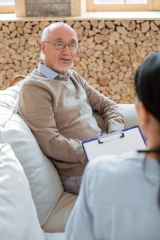 Мое благополучие. вид сверху веселого жизнерадостного пожилого мужчины, сидящего на диване в очках и делящегося мыслями с врачом