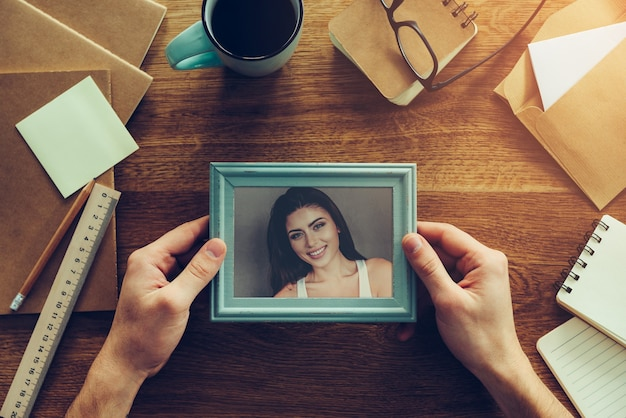 My wife is my inspiration. close-up top view of man holding photograph of beautiful young woman over wooden desk with different chancellery stuff laying around