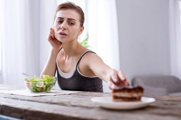 Мое желание. подавленная молодая женщина хочет торт, находясь на диете
