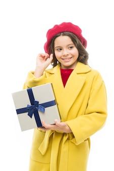 私のウィッシュリスト。チャイルドスタイリッシュホールドギフトボックス。女の子のかわいい小さな女性のコートとベレー帽は贈り物を運びます。春の買い物のコンセプト。春の季節に向けて洋服やかわいいギフトを購入しましょう。満足のいく買い物の日。