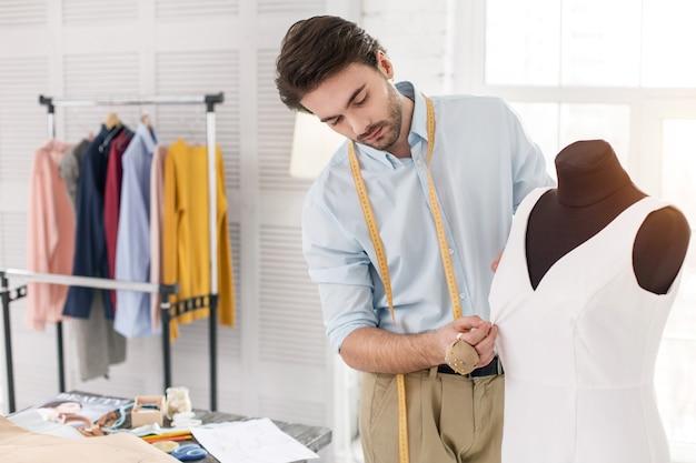 내 근무일. 그의 사무실에서 일하고 새 드레스를 만드는 쾌활한 젊은 재단사