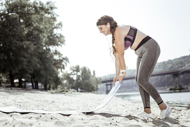 私のトレーニング。トレーニングの準備をしながらヨガマットを持って喜んで素敵な女性
