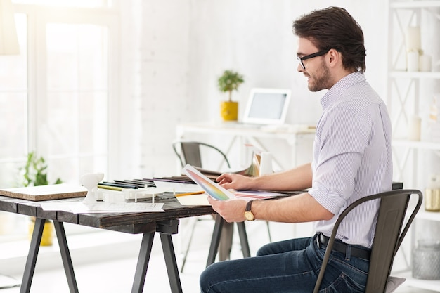 Мое рабочее место. сосредоточенный бородатый мужчина сидит за столом и держит несколько листов бумаги