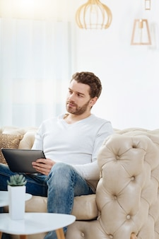 My workplace. confident handsome self employed man sitting on the sofa and holding a tablet while working in his office