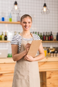 내 직장. 카페테리아에서 일하는 동안 유니폼을 입고 메모를 작성하는 행복 긍정적 인 젊은 여자