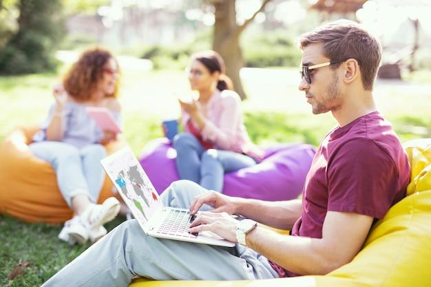 내 직장. 좋은 집중된 남자가 의자에 앉아 자신의 노트북에서 작업 프리미엄 사진