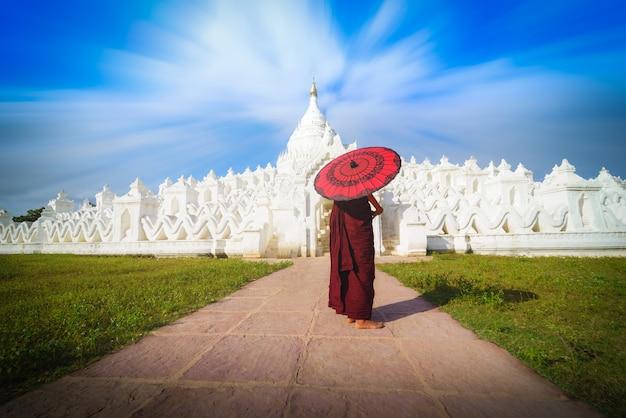 Азиатский молодой монах, держащий красные зонтики в mya thein tan pagoda в mingun