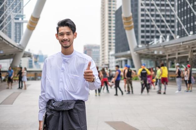Бизнесмен из мьянмы улыбаются с большими пальцами руки вверх позы на размытом фоне группы людей