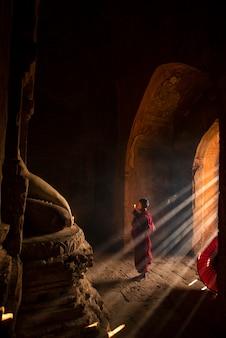 Myanmar novice monk pray respect to myanmar buddhist statue in myanmar temple, old bagan, myanmar