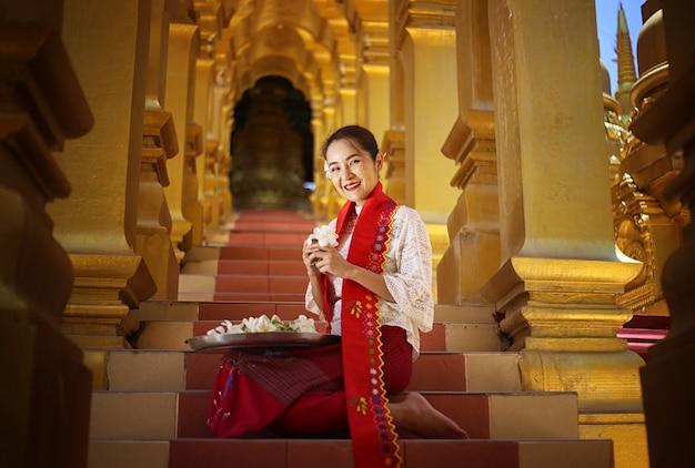 寺院で花を持っているミャンマーの女性。仏教寺院を訪れるビルマの伝統的なドレスを着た東南アジアの若い女の子