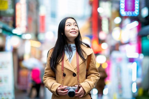 Молодой азиатский путешественник женщины путешествуя и делая покупки улица myeongdong