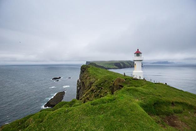 Mykines lighthouse, faroe islands. foggy view of old lighthouse