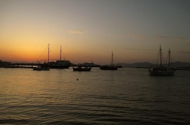 ミコノス島、ギリシャの美しい夕焼け空の下でミコノス旧港
