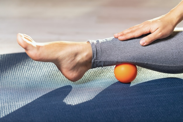 Myofascial relaxation of the leg muscles with a massage ball on a gymnastic mat at home prevent leg fatigue