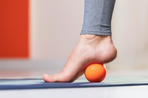 Myofascial relaxation of the muscles of the foot with a massage ball on a mat at home closeup