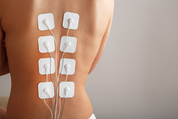 Myostimulation electrodes on a woman's back for massage and rehabilitation. treatment, weight loss.