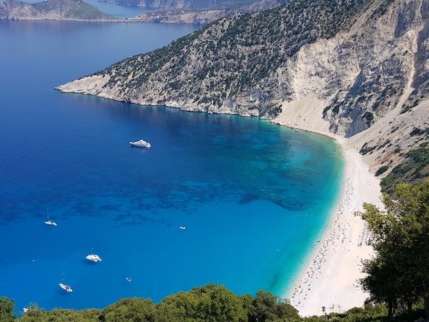 Пляж миртос в окружении моря под лучами солнца в греции