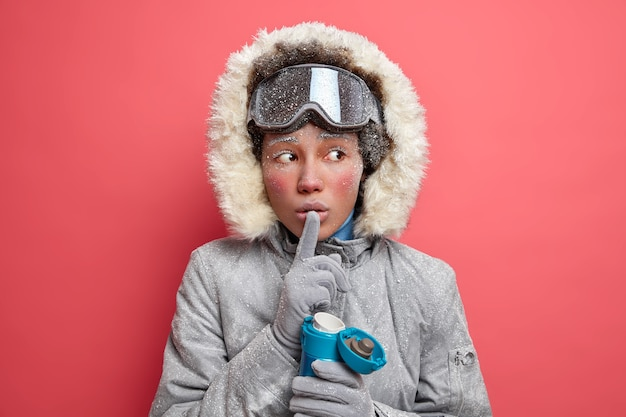 Mysterious active woman makes silence gesture and tells secret looks away and tries to warm with hot beverage has red icy face dressed in winter outerwear.