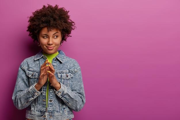 신비한 아프리카 여자가 손가락을 뾰족하게하고 무언가에 힌트를 주며 호기심 많은 의도를 가지고 있습니다.